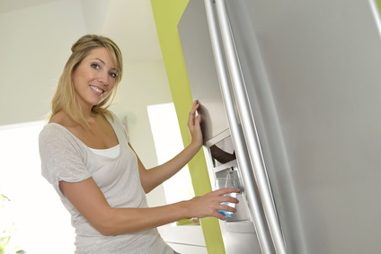 woman getting fresh water from fridge